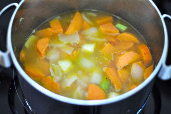 Adding stock to sweet potato and veg